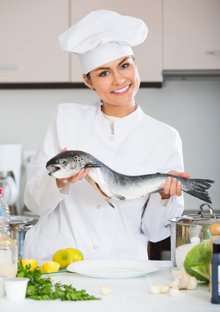 corcovado: Young chef holding rainbow trout in professional kitchen Foto de archivo