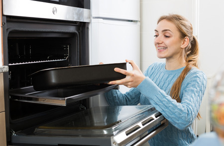 18's: Portrait of cheerful girl putting baking tray in kitchen oven Stock Photo
