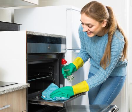 mucama: dama joven que hace el horno de limpieza en la cocina doméstica Foto de archivo