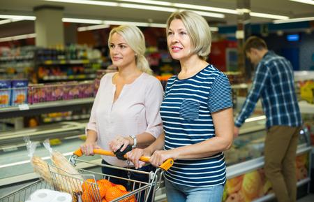 55 60: Practical women choosing frozen meat in food store