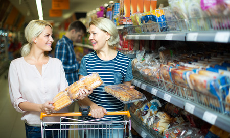 25 35: Two smiling women buying bread and pastry in food shop