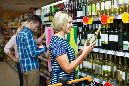 55 60: Happy mature woman at wine section in hypermarket Stock Photo