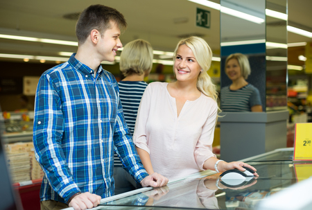 25s: Happy smiling young couple buying frozen food in grocery store Stock Photo
