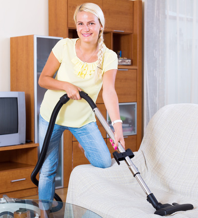 cleanup: european  woman using vacuum cleaner during regular clean-up