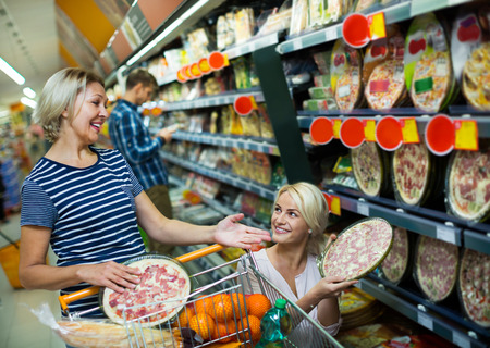 25 35: Adult girl helping senior mother in a pizza section of a supermarket Stock Photo