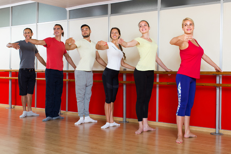 barre: Group of smiling spanish men and women practicing at the ballet barre