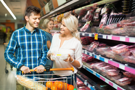25 35: Smiling young family couple choosing chilled meat in food store