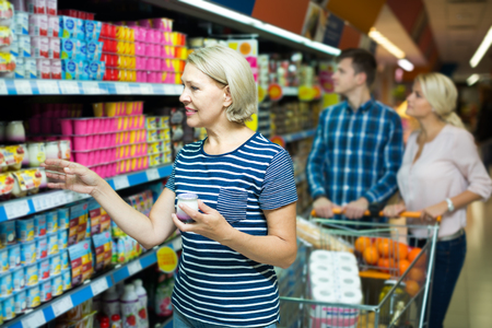25 35: russian female customers choosing fruit yoghurt and pudding at store