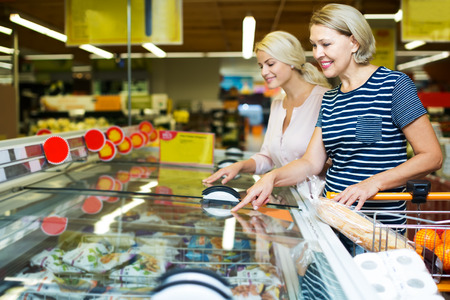 55 60: Smiling women buying frozen vegetables in grocery store