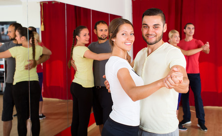 unprofessional: Beautiful woman dancing a slow dance with a handsome man in dancing studio with other dancing couples in background Stock Photo