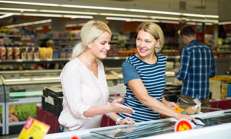 55 60: women choosing frozen meat in food store