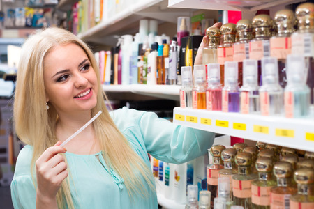 eau de perfume: Cheerful smiling blond girl buying perfume in fragrance section of supermarket