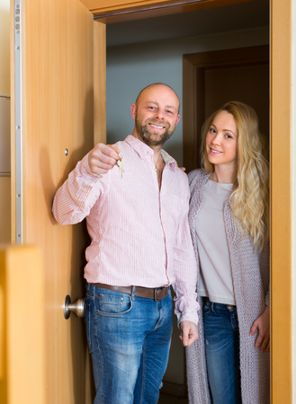 hypothec: Joyful smiling married couple coming to see new flat. Focus on man