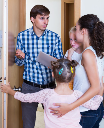 Young landlord standing indoors and asking family of tenants for money Stock Photo