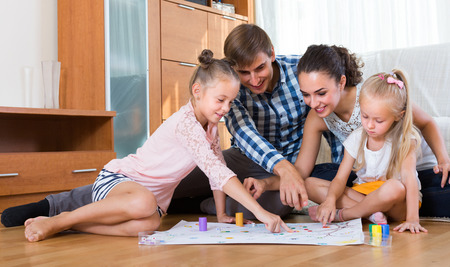 Happy young parents and two little daughters playing board game at home