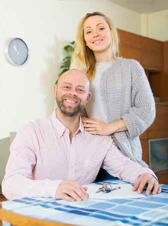 hypothec: Smiling married couple sitting at table with keys and documents