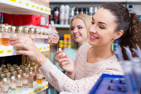 eau de perfume: Portrait of young smiling female customers shopping in beauty store Stock Photo
