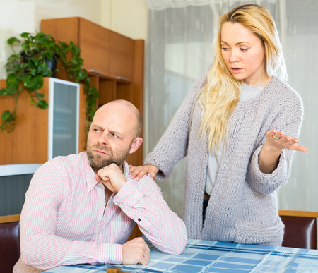 nags: Family problem: attractive young wife nags her adult husband. He is sitting turned away from her. Focus on man