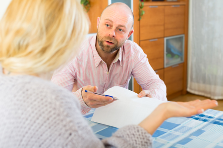 covetous: Adult man asks woman to sign a financial document Stock Photo