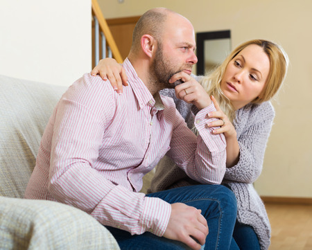 fracas: Sad adult man has problem, woman consoling him on sofa at home. Focus on men