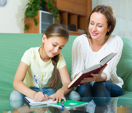 10 12: teenager and mother together doing homework in home