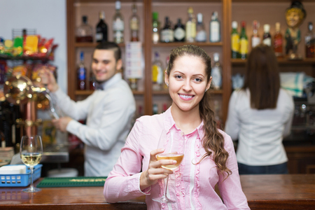 bartenders: Happy woman drinking wine at counter and chatting with bartenders