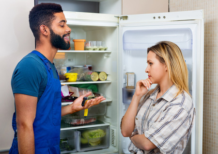 complaining: White woman complaining to black handyman on problems with fridge