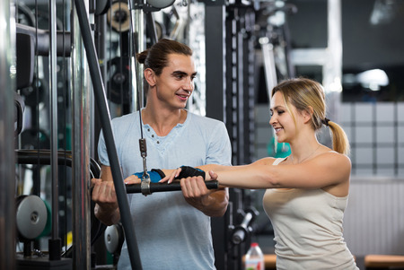 anaerobic: happy spanish adults having strength training under coach control in gym
