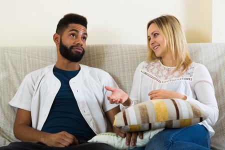 blabbing: Young interracial couple talking in domestic interior