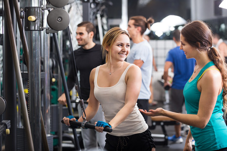 25 35: Young adults doing powerlifting on a machines in the fitness club