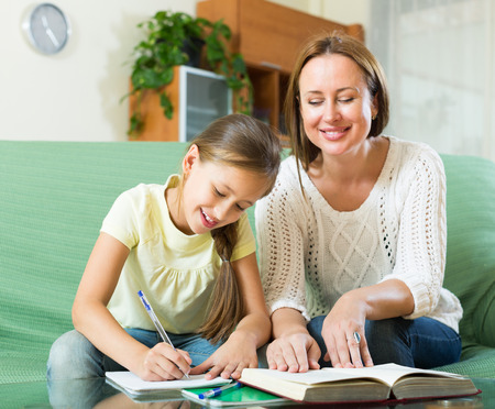 9 10 years: Happy mother with smiling schoolgirl doing homework at home. Focus on girl Stock Photo