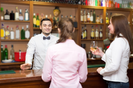 barmen: Smiling young bartender and happy women at bar Stock Photo