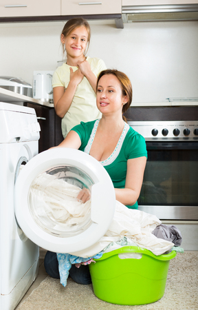 schoolgirl: Home laundry. Positive woman with playful daughter using washing machine at home Stock Photo