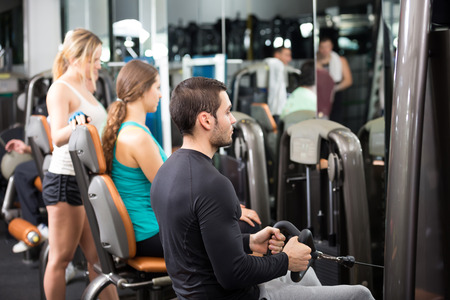 25 35: Group of smiling young adults doing powerlifting on machines in fitness club