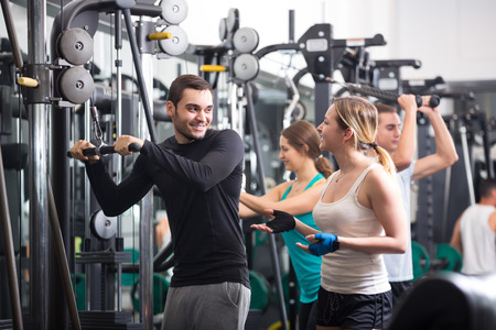 powerlifting: Positive smiling young adults doing powerlifting on machines in modern fitness club Stock Photo