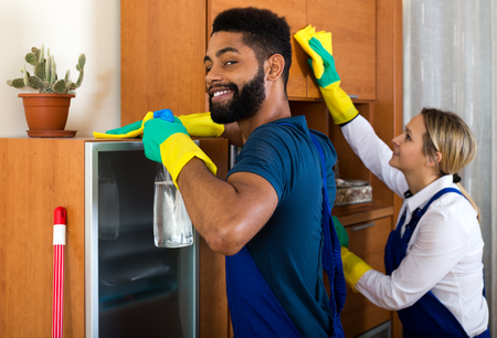cleaning team: Happy cleaners cleaning and dusting in ordinary house Stock Photo