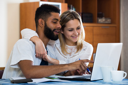 black person: Happy smiling couple filling forms of banking application in domestic interior. Focus on guy