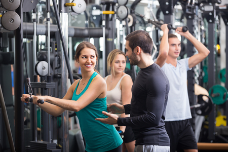 25 35: Happy young adults doing powerlifting on machines in gym Stock Photo