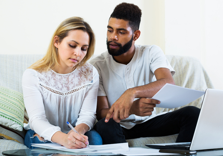 25 35: Interracial young couple filling papers for mortgage indoors