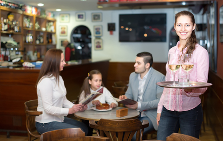barmen: happy nippy with beverages and bar crew at background Stock Photo