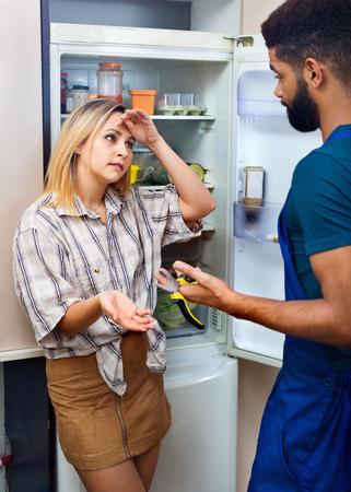 30 35: White upset woman complaining to black handyman on problems with fridge