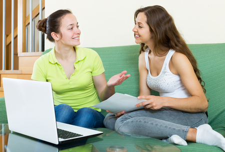 parsimony: women looking financial documents with laptop  in home interior