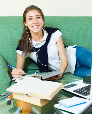 18 20: Smiling young girl using laptop in flat Stock Photo