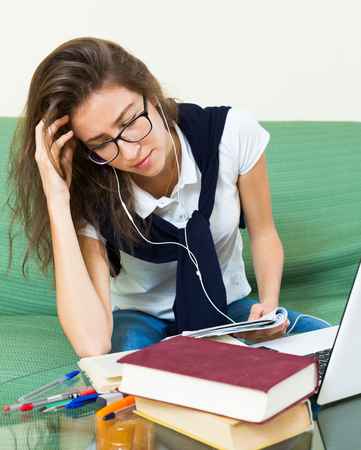 18 20: Nervous teenager doing homework on the couch Stock Photo