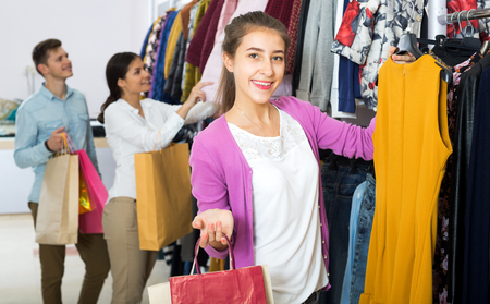 liked: Positive young female shopper chooses liked things in the boutique