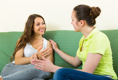 gesticulate: Two smiling young female friends gossiping on sofa in home interior
