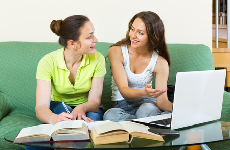 cognate: Two young  funny girls studying in home