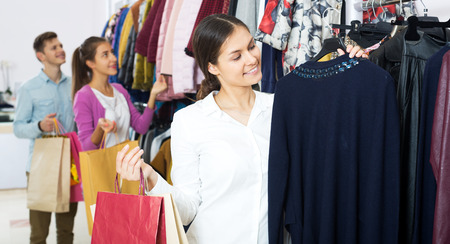 liked: Attractive woman customers chooses liked things in the boutique
