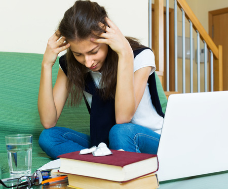 18 20: Upset young girl study at home behind her laptop