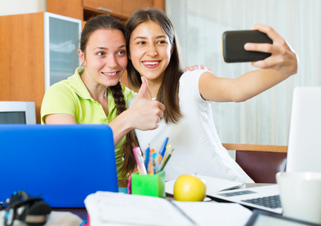 avocation: Happy student girls sitting at the table and making photo on a mobile phone Stock Photo